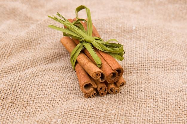 Кулинарные специи. палочки корицы на грубой ткани коричневого цвета из джутовой или льняной ткани.