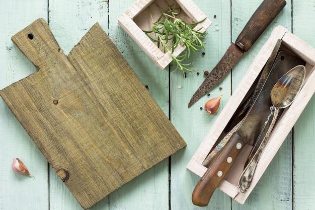 나무 식탁에 요리 표면 커팅 보드 마늘과 로즈마리 복사 공간 평면 누워 평면도