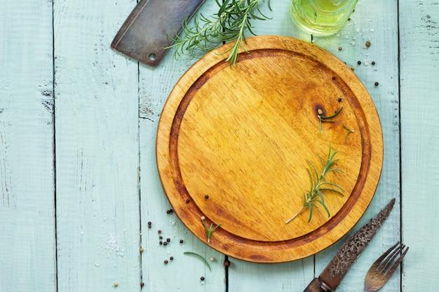 요리 표면 커팅 보드 나무 식탁에 다양한 향신료와 로즈마리 복사 공간 평면 누워 평면도