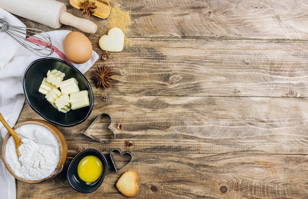Culinary table ingredients for cooking on wooden kitchen table.