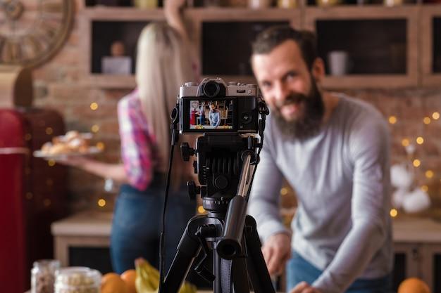 요리 동영상 블로그. 커플 비즈니스와 라이프 스타일. 남자와 여자 다락방 부엌 요리. 팟 캐스트 촬영. 삼각대에 카메라.