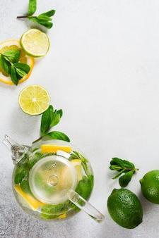 さわやかな飲み物のレモネード、モヒート、または冷たいさわやかなお茶のための料理の壁。新鮮なレモン、ライム、ザクロ、乾燥茶バラの花、お茶、サトウキビ、ミントの花束の葉