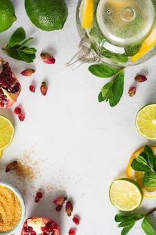 Кулинарная стенка для прохладительных напитков лимонада, мохито или холодного освежающего чая. свежий лимон, лайм, гранат, сушеные цветы чайной розы, чай, тростниковый сахар и листья мяты.
