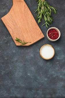 料理の壁。木製のまな板、ローズマリー、海の塩、灰色の石造りのキッチンテーブルの上のピンクのコショウ。フラットコピースペースを置きます。
