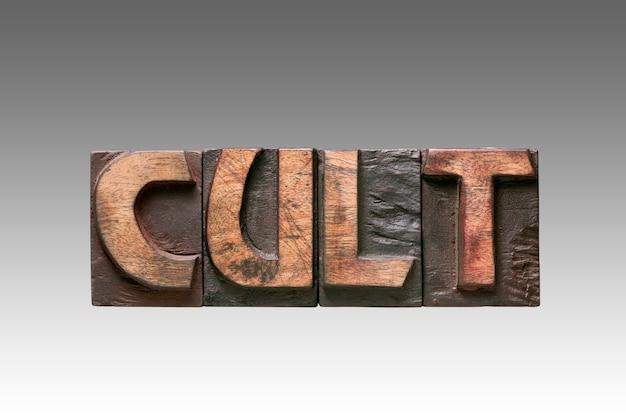그라데이션 배경에 고립 된 빈티지 나무 활자 문자로 조립 된 컬트 단어