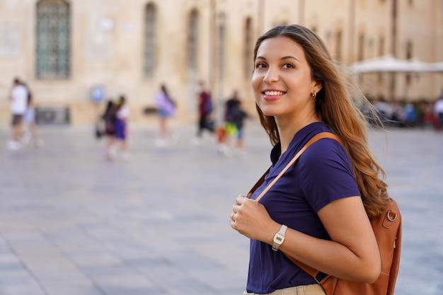 ヨーロッパの文化旅行。歴史的なヨーロッパの街を一人で散歩する魅力的な女の子。