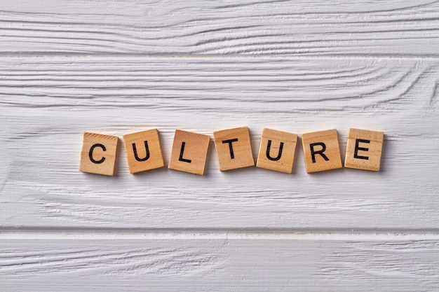 文化と文明の概念。特定の国または他の社会集団の業績。木製の背景で隔離のアルファベットの立方体の文字。