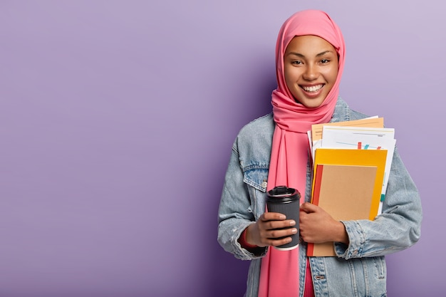 Culture, religion and studying concept. glad muslim woman with toothy smile, carries notebook with papers, takeaway coffee