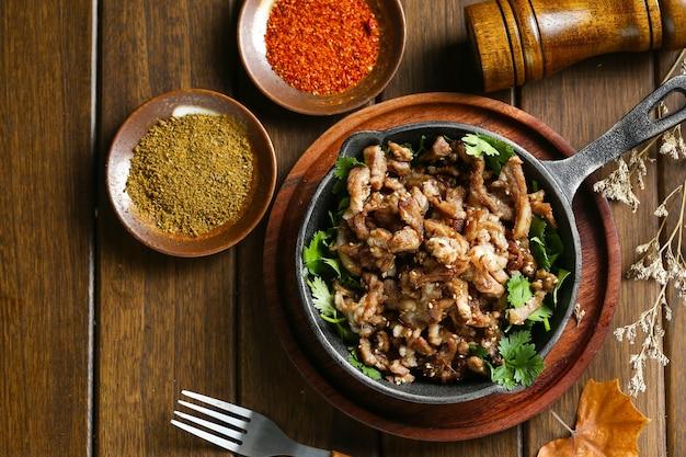 Жареный ягненок с тмином в горшочке на деревянном столе