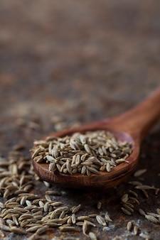 織り目加工の背景に木のスプーンでクミンの種子