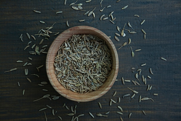 Cumin seeds in a wooden dish.