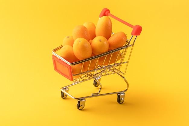 黄色の背景、フルーツショッピングコンセプトのショッピングカート内のキンカンまたはキンカン