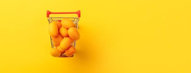 黄色の背景のショッピングカート内のキンカンまたはキンカン
