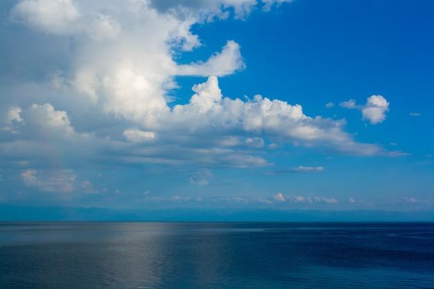 Кучевые облака на фоне голубого неба над озером байкал. горизонтальное изображение.