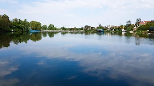 Кучевые облака и небо отражаются в воде озера в солнечный летний день. красивый природный ландшафт.