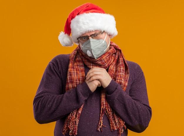 Astuzia uomo adulto che indossa occhiali maschera protettiva e cappello santa con sciarpa intorno al collo tenendo le mani insieme guardando la telecamera isolata su sfondo arancione