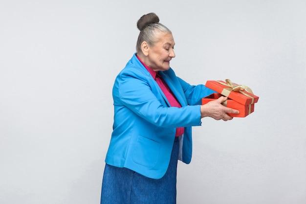 교활한 나이 든 여자는 선물 상자를 들여다 봅니다.