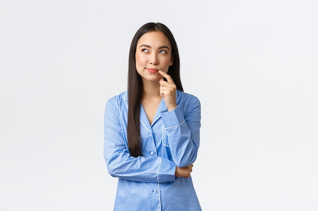 Хитрая и задумчивая симпатичная азиатская девушка в синей пижаме, ухмыляется и смотрит в левый верхний угол, что-то воображает, имеет интересную идею, стоит на белом фоне в джемми