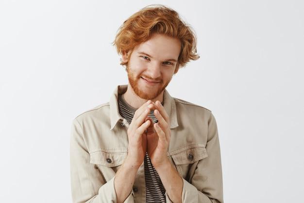 白い壁に向かってポーズをとる狡猾なひげを生やした赤毛の男