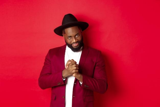 교활한 흑인 남자는 아이디어를 가지고 있고, 사악한 미소를 지으며 손을 문지르며, 빨간색 배경에 서서 음모를 꾸미고 있습니다.
