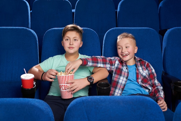 Cunning boy stealing popcorn while friend watching film