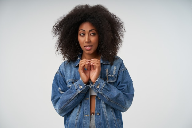 Cunning dark skinned lady in white top and jeans coat folding raised hands as she ploting something, looking aside and squinting, isolated on white