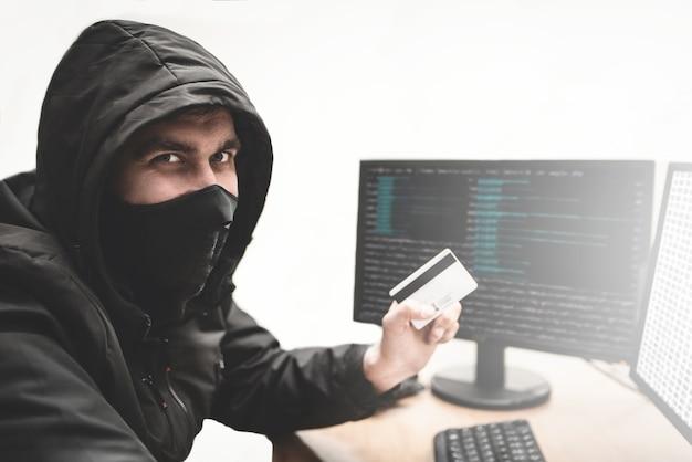 Хитрый хакер-мошенник на белом фоне с украденной кредитной картой в руке пытается украсть деньги с банковского счета. концепция кражи в интернете