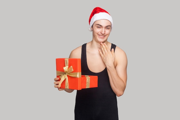 Хитрый человек в красной шляпе, держащий подарочную коробку, касаясь его подбородка и зубастой улыбкой, смотрящей в камеру с забавным лицом. закрытый, студийный снимок, изолированный на сером фоне Premium Фотографии