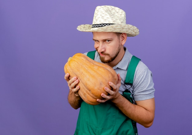 Cunning young handsome slavic gardener in uniform and hat holding butternut pumpkin  isolated on purple wall with copy space