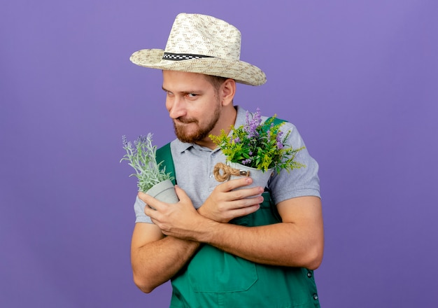 Cunning young handsome slavic gardener in uniform and hat holding flowerpots keeping hands crossed  and biting lip isolated on purple wall with copy space