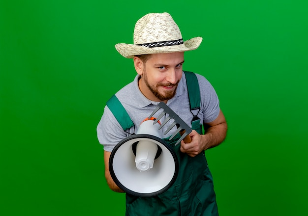 Cunning young handsome slavic gardener in uniform and hat holding speaker and rake looking  isolated on green wall with copy space