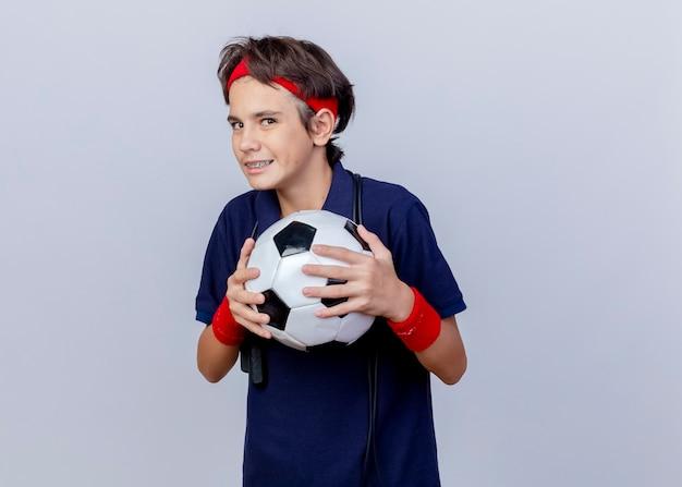 Astuzia giovane ragazzo sportivo bello che indossa fascia e braccialetti con bretelle dentali e corda per saltare intorno al collo tenendo il pallone da calcio guardando la telecamera isolata su sfondo bianco con spazio di copia