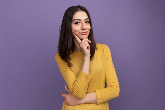 Cunning young pretty caucasian girl putting hand on chin isolated on purple wall with copy space