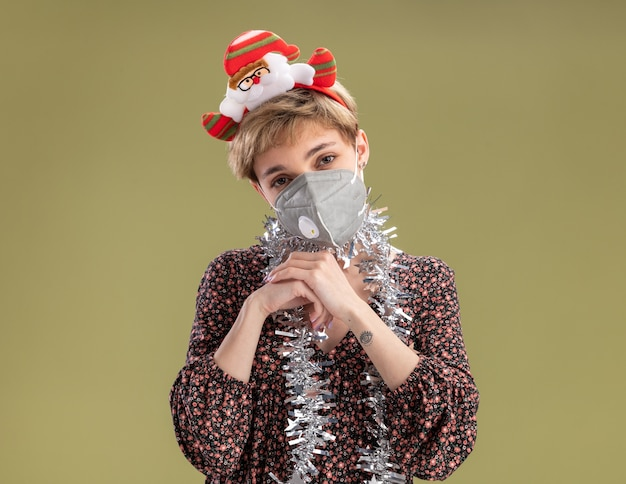 Cunning young pretty girl wearing santa claus headband and tinsel garland around neck with protective mask looking at camera keeping hands together isolated on olive green background