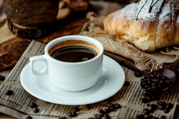 Cup of americano coffee placed on newspaper