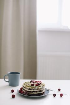 Чашка и торт, украшенный ягодами на белом столе Premium Фотографии