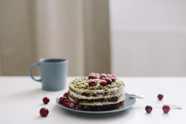 Чашка и торт, украшенный ягодами на белом столе
