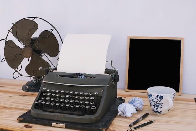 タイプライターとファンの近くのカップと黒板