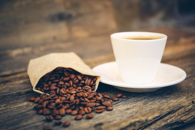 Чашка и кофейные зерна выпадают из пакета на старой деревянной поверхности