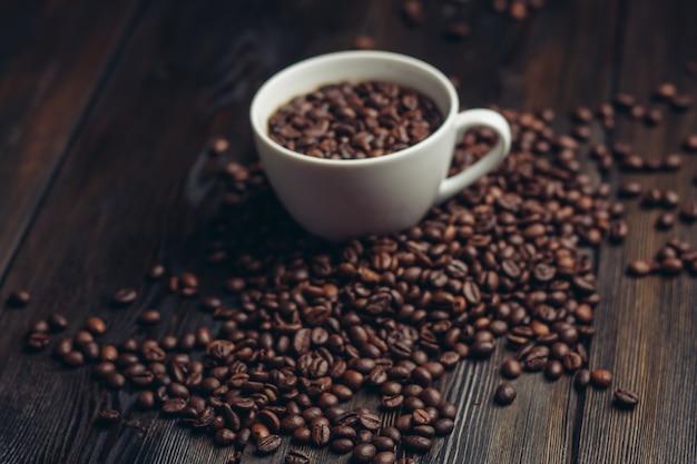 木製の背景の香りのカップ&ソーサーコーヒー豆