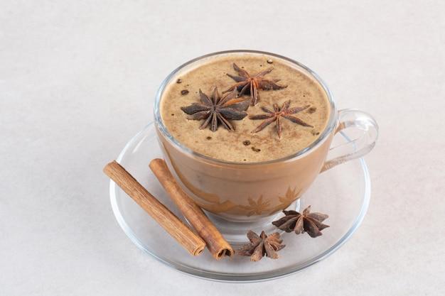 Una tazza di caffè dall'aroma gustoso con bastoncini di cannella e anice stellato. foto di alta qualità