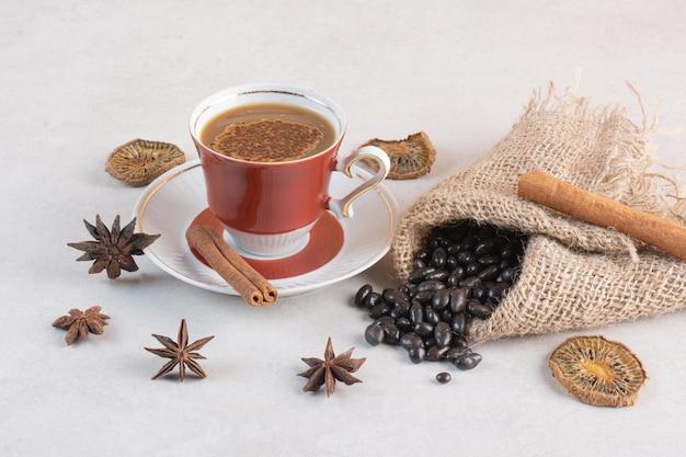 Una tazza di caffè dall'aroma gustoso con bastoncini di cannella e anice stellato