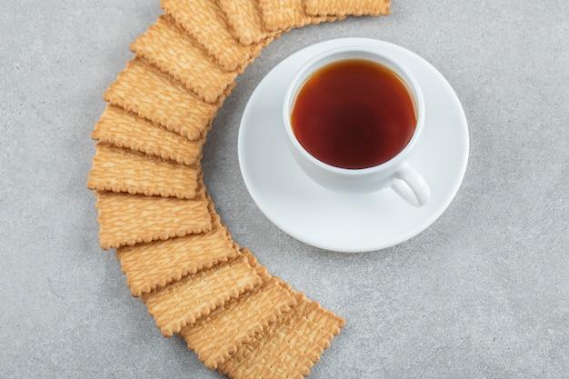 Una tazza di tè aromatico con cracker su una superficie grigia.