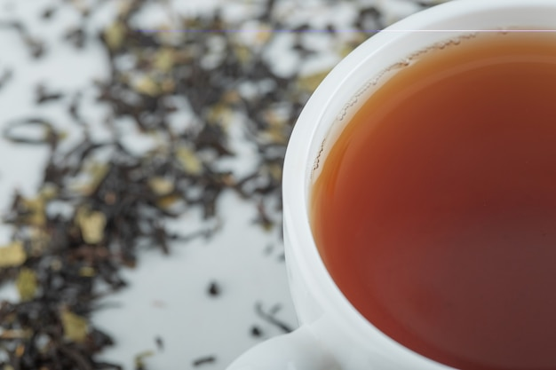 A cup of aroma tea with dried loose teas.