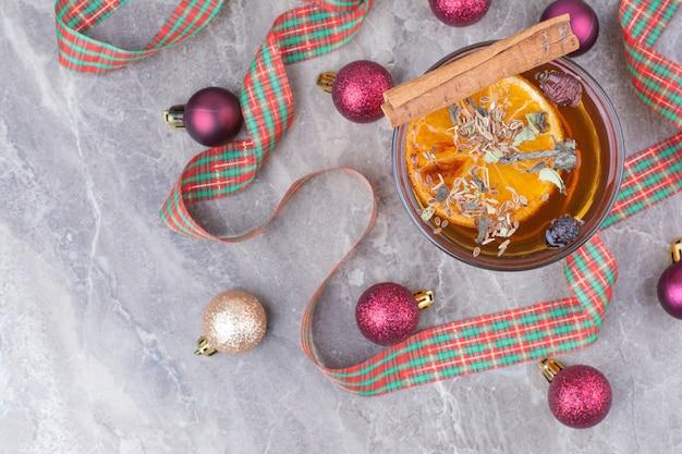 Tazza di tè aromatizzato con presente e fiocco su fondo in marmo.
