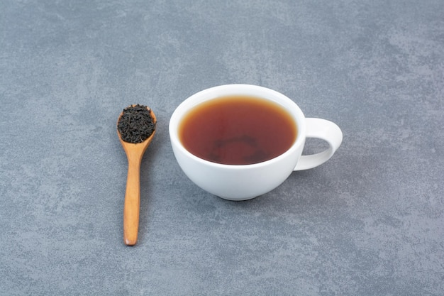 A cup of aroma tea with wooden spoon of infusion