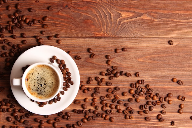 Cup of aromatic coffee and coffee beans on a wooden background