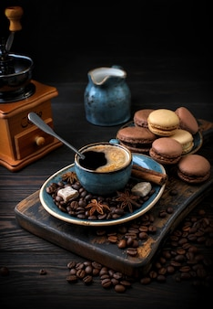 A cup of aromatic coffee with macaroons on a dark wooden board