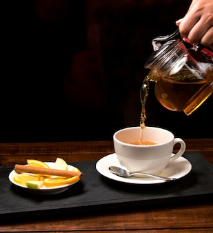 Cup of aromatic tea and bowl with lemon