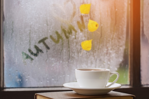 Cup of autumn tea, coffee, chocolate and yellow leaves on rainy window. hot drink for autumn mood.